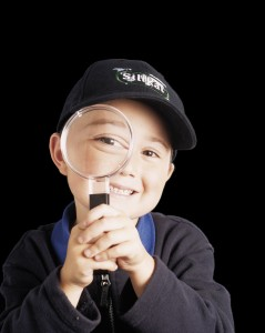 Boy with magnifying glass exploring top coat cement choices