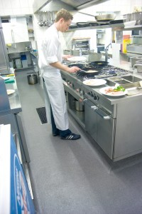 Employee standing on kitchen floor cooking on stove.