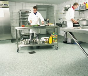 Flake type of kitchen flooring with chefs cooking.