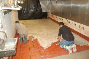 A KFC restaurant with tiles being covered by contractor.