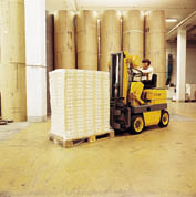 Man on forklift driving across industrial flooring.
